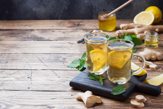 Two cups of natural herbal tea ginger lemon mint and honey on a wooden surface. Premium Photo