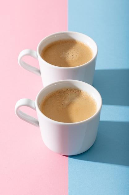 파스텔 핑크와 파란색 배경에 커피 두 잔, 대비 그림자가있는 사진 프리미엄 사진