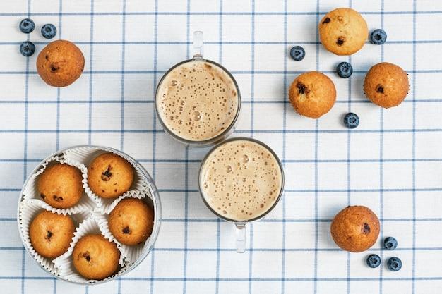 市松模様のテーブルクロスに泡状のコーヒーとブルーベリーのマフィンの2つのカップ。 Premium写真