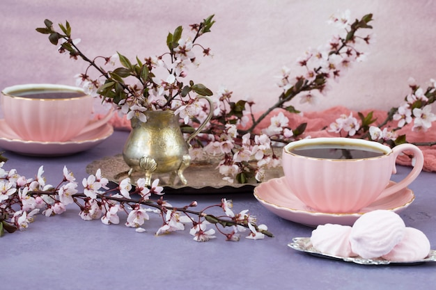Two cups of tea in pink dishes, meringues and cherry blossoms in an old vase - tea time Premium Photo