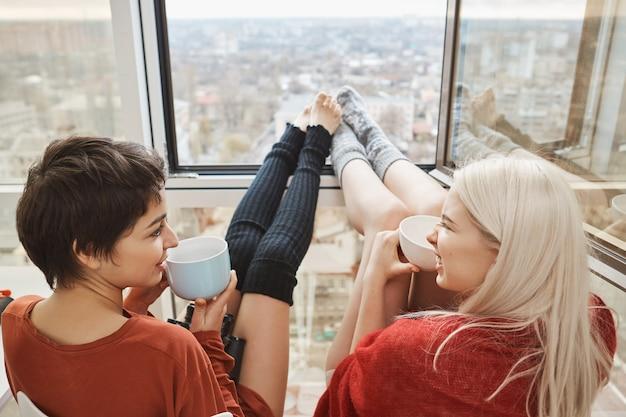 Две милые и счастливые женщины сидели на балконе, пили кофе и болтали с вытянутыми ногами, которые опирались на окна. подруги рассказывают о планах на сегодня, хотят пропустить работу и остаться дома Бесплатные Фотографии