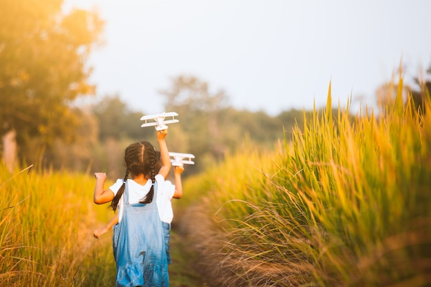 Two cute asian child girls running and playing with toy wooden airplane in the field Premium Photo