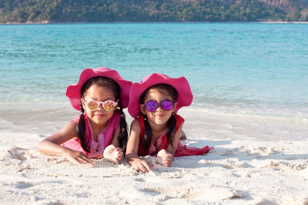 Two cute asian child girls wearing pink hat and sunglasses playing with sand together on the beach Premium Photo
