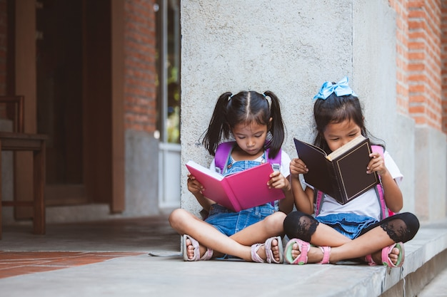 Two cute asian pupil girls reading a book  together in the school with fun and happiness Premium Photo