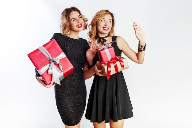 Две милые празднования женщины, держащей большие новогодние подарочные коробки. удивительные лица. в элегантном черном платье. Бесплатные Фотографии