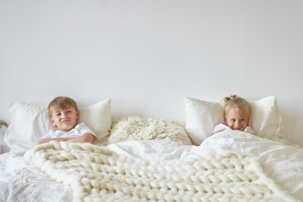 Two cute children relaxing in bedroom. indoor shot of teen boy in pajamas lying on bed with his blonde little brother on the other side, having playful looks. childhood, kids and family concept Free Photo