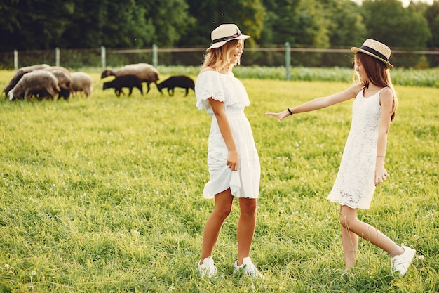 Two cute girls in a field with a goats Free Photo