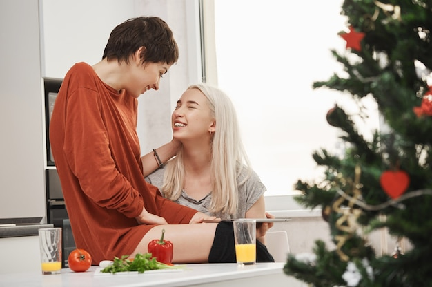 Two cute girls sitting in kitchen while talking and laughing during breakfast near christmas tree. typical happy morning of tender girlfriends in relationship who live together Free Photo