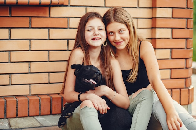 Two cute girls in a summer park with a dog Free Photo