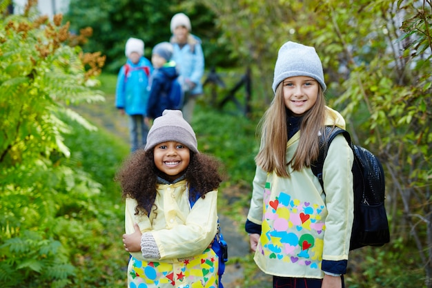 Two cute girls on the way to school in autumn Free Photo