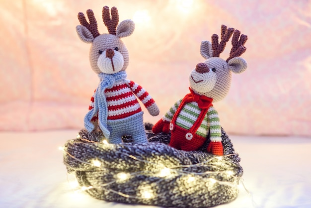 Two cute holidays deers in striped sweaters with christmas lights around on the pink . Premium Photo