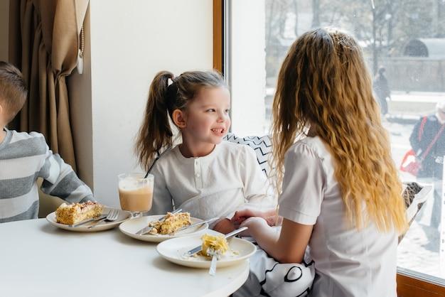 두 명의 귀여운 소녀가 카페에 앉아 화창한 날에 놀고 있습니다. 레크리에이션과 라이프 스타일. 프리미엄 사진