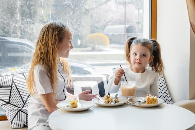 두 귀여운 소녀는 카페에 앉아 화창한 날에 놀고있다 프리미엄 사진
