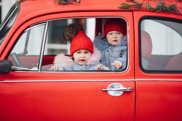 Двое милых маленьких детей в зимней одежде выглядывают из окна ярко-красной машины Бесплатные Фотографии