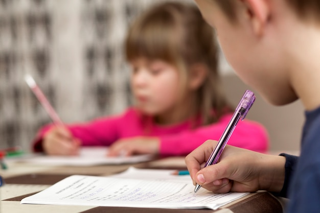 Two cute young children, boy and girl, brother and sister doing homework, writing and drawing at home on blurred. Premium Photo