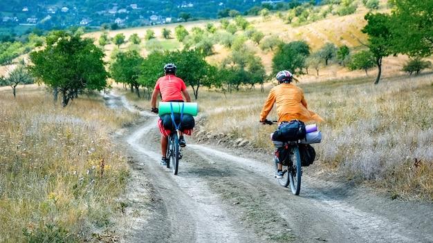 Due ciclisti in caschi con biciclette piene di roba da viaggiatore che si muovono sulla strada di campagna tra rari alberi verdi Foto Gratuite