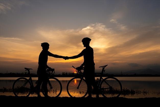 Два велосипедиста, пожимая руку после финиша, едут на велосипеде вместе. концепция спортивного мастерства. Premium Фотографии