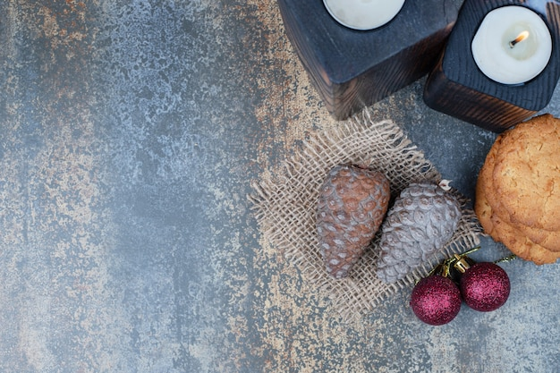 Two dark candles with cookies, two red balls and pinecones on marble background. Free Photo