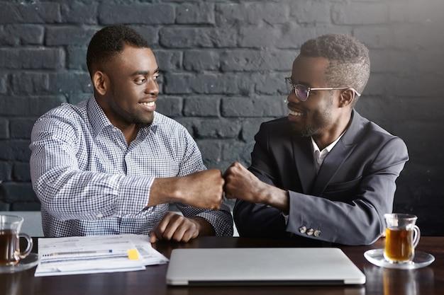 お互いに拳のバンプを与えるフォーマルな服装の2人の浅黒い肌のビジネスマン 無料写真
