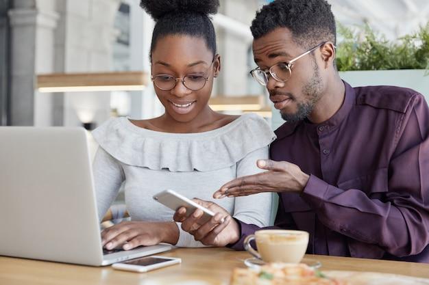Два темнокожих административных менеджера мужского и женского пола проверяют сообщения на сотовом, клавиатуру портативного компьютера, проверяют информацию Бесплатные Фотографии