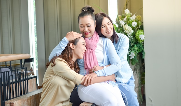Two daughters embracing fragrant mother with love Premium Photo