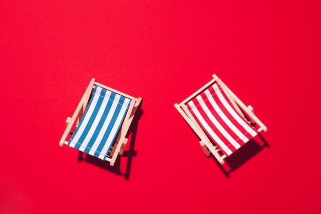 Two deck chairs with hard shadow on red paper background. Premium Photo