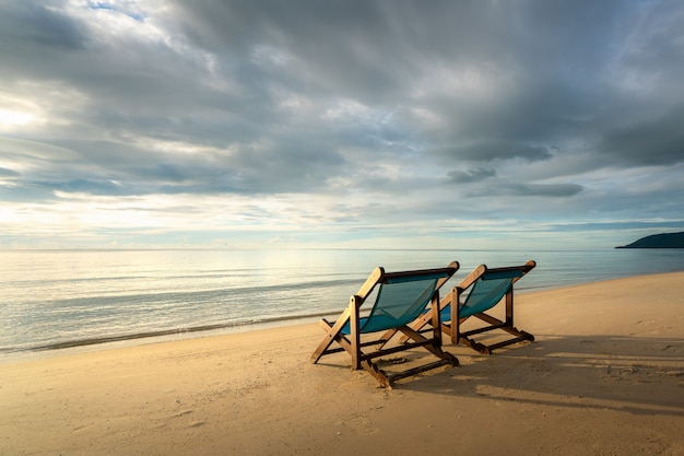Two deckchairs on the beach at sunset with a tropical sea Premium Photo