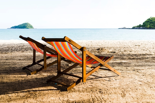 Two deckchairs on sandy beach Free Photo