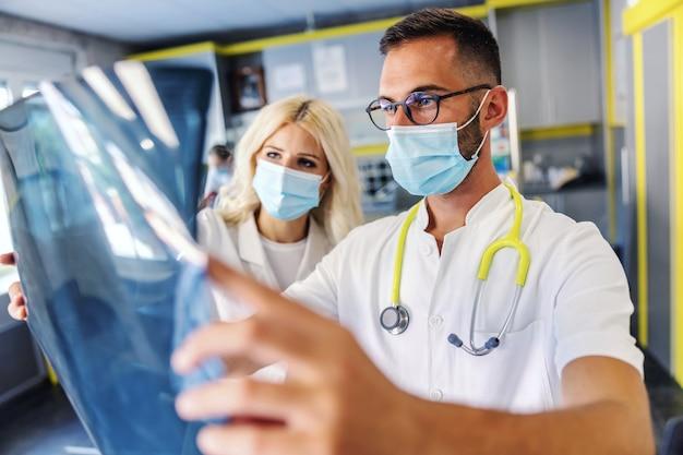 Два преданных трудолюбию и умные коллеги держат рентгеновский снимок легких пациента и смотрят на него. Premium Фотографии