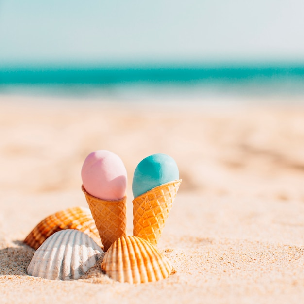 Two delicious ice creams with shells in the beach Free Photo