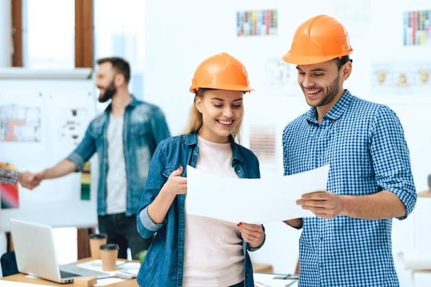 Two designers architects posing with papers. Premium Photo