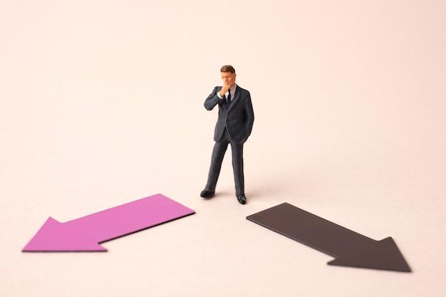 ミニチュアビジネス男と2つの方向矢印 Premium写真
