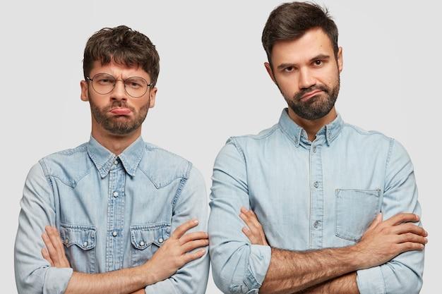 Due ragazzi scontenti tengono le braccia conserte, guardano con espressione cupa, si sentono perdenti dopo aver perso il gioco, vestiti con abiti di jeans alla moda, stanno uno accanto all'altro sul muro bianco. Foto Gratuite
