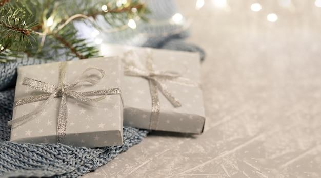 Две подарочные коробки своими руками на сером вязаном пледе с еловыми ветками и рождественскими огнями. Premium Фотографии