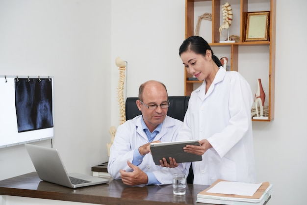 Two doctors analyzing digital x-ray on tablet pc Free Photo
