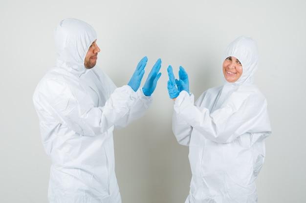 Due medici che applaudono le mani in tute protettive Foto Gratuite