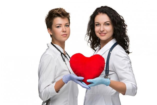 赤いハートを保持している2人の医師 無料写真