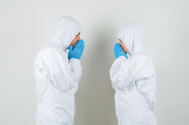 Due medici che tengono le mani nel gesto di preghiera in tute protettive Foto Gratuite