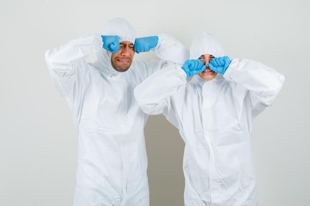 防護服を着た2人の医師、子供のように泣きながら怖がっている手袋が目をこすります 無料写真