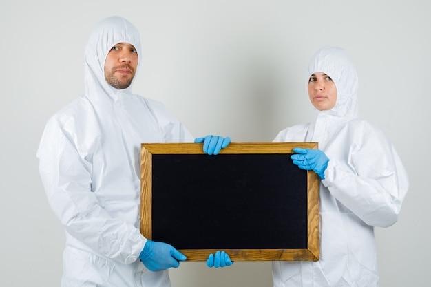 Due medici in tute protettive, guanti che tengono lavagna e che sembrano fiduciosi Foto Gratuite