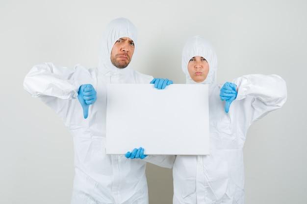 Due medici in tute protettive, guanti che tengono tela bianca Foto Gratuite