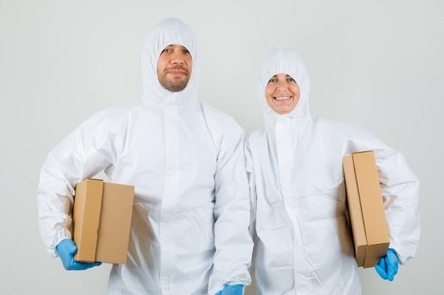 Due medici in tute protettive, guanti che tengono scatole di cartone e che sembrano allegri Foto Gratuite