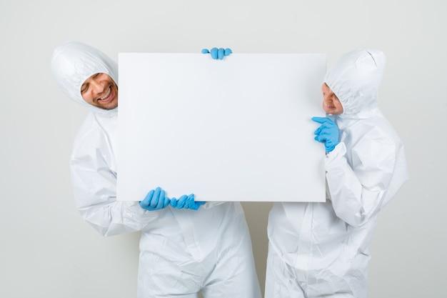 Due medici in tute protettive, guanti che tengono tela vuota e che sembrano allegri Foto Gratuite