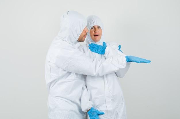 Due medici in tute protettive, guanti che guardano qualcosa di inaspettato Foto Gratuite
