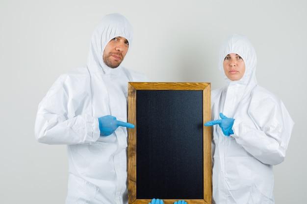 Due medici in tute protettive, guanti che puntano alla lavagna e che sembrano sicuri Foto Gratuite