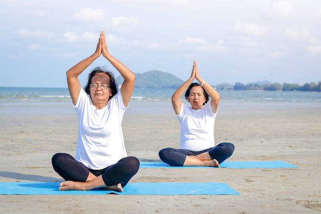 Two elderly women are exercising at the seaside beach, sitting and doing yoga. Premium Photo