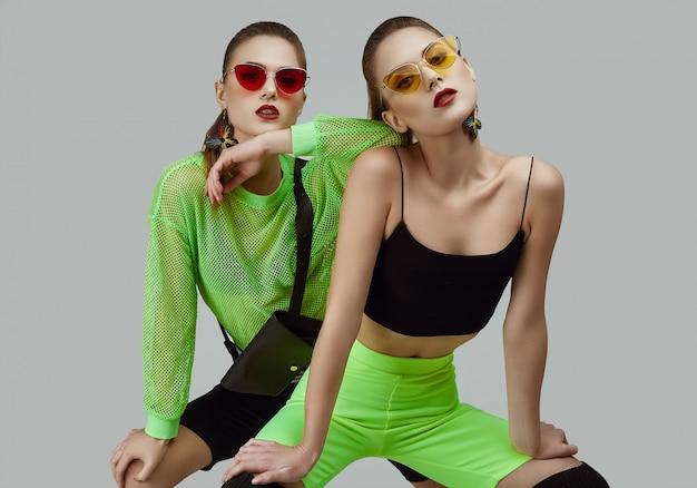 Two elegant glamor hipster twin girls in fashion neon green dresses Premium Photo