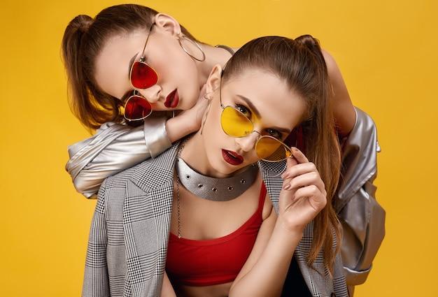 패션 레드 탑, 검은 색 반바지에 두 우아한 매력 힙 스터 쌍둥이 소녀 프리미엄 사진