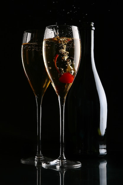 Two elegant glasses with champagne and cherry Free Photo