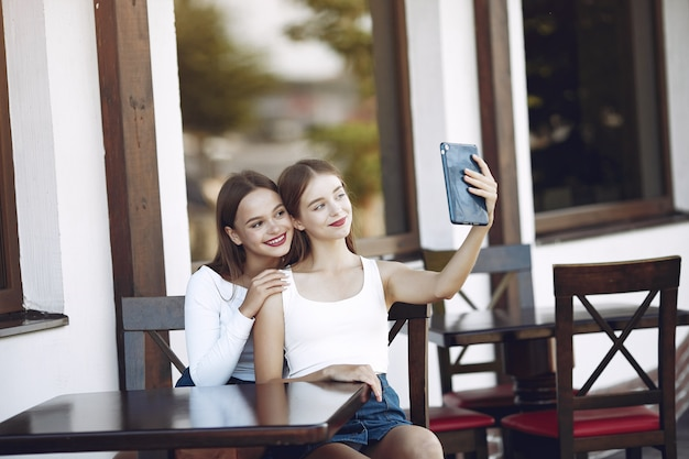 Two elegant and stylish girls in a summer cafe Free Photo